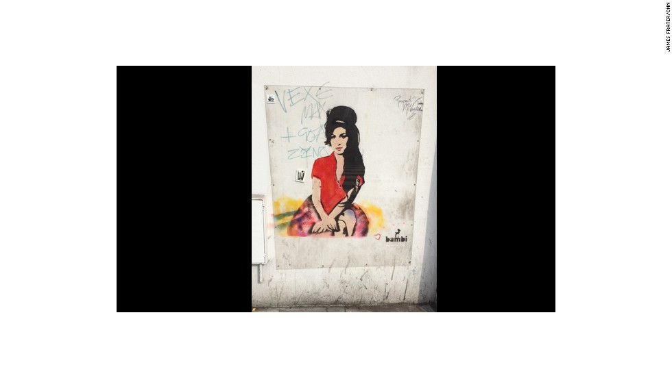 Some of her works are now deemed culturally significant. Some, like this one depicting Amy Winehouse, are protected under plastic sheets.