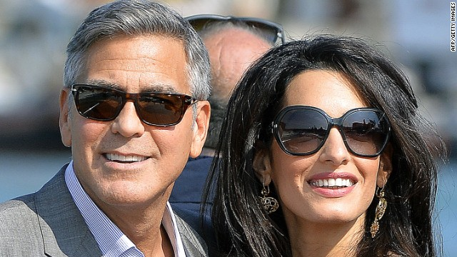 George Clooney ( L) and his fiancee Amal Alamuddin take a taxiboat upon their arrival in Venice on September 26, 2014, on the eve of their wedding.