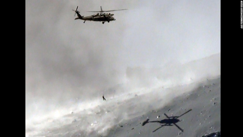 A helicopter lifts a survivor from the ash-covered top of Mount Ontake.