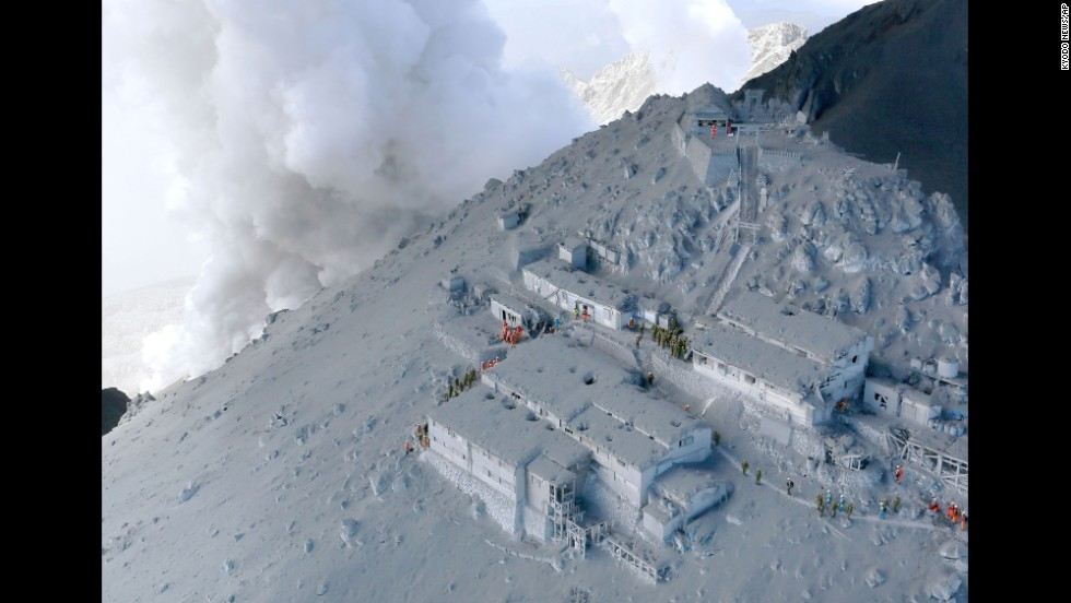 Firefighters and members of Japan's military conduct a rescue operation at a mountain lodge near the peak of Mount Ontake.