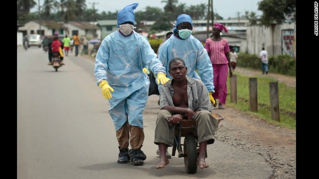Residents of the St. Paul Bridge neighborhood wearing personal protective equipment take a man suspected of carrying the Ebola virus to the Island Clinic in Monrovia, Liberia, on Sunday September 28.