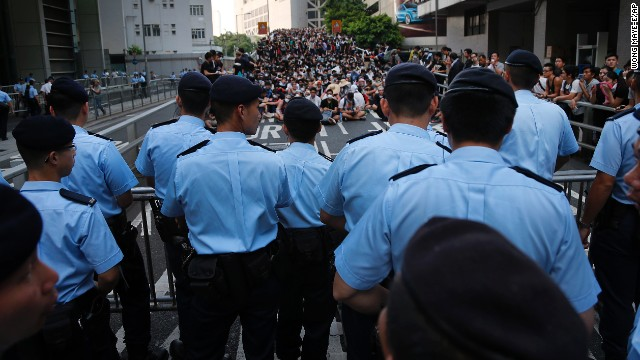 Pro-democracy protesters sit on a road as they face-off with local police on September 29.