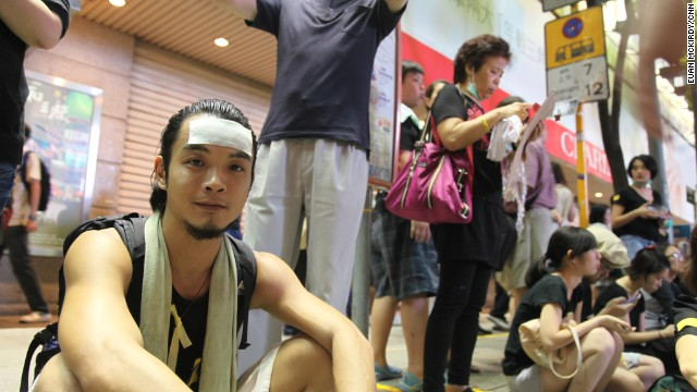 """Chung, 30, has been here 2-3 hours. Too many people in Admiralty, he says. He's an actor, here with a group of friends. Wearing cooling strip on his forehead (lots of people wearing these, pretty hot night) . Needs to work tomorrow. Haven't seen any police. """"Keep alert to everyone, everywhere. Undercover cops here for sure."""" He went to Admiralty two days ago, Mong Kok yesterday. """"No way CY will change his mind. I tutor drama so when I see students on the street I get upset and as an adult I need to come out to support - to stand in front"""""""