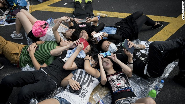 Protesters look at their mobile phones while occupying an intersection in Hong Kong's Mong Kok district on September 29, 2014.