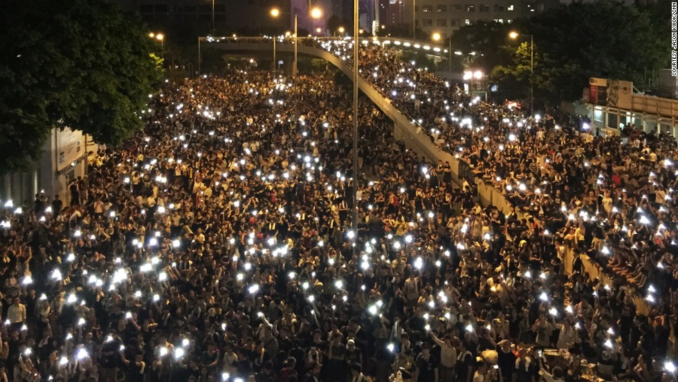 Photographed from above, the glowing screens of mobile phones held aloft by the sea of protesters' have created an enduring image of solidarity.