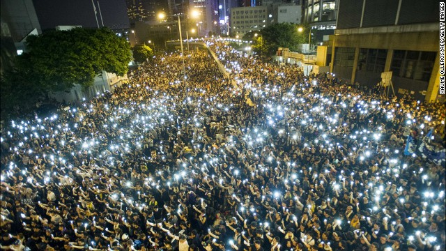 Protestors hold up their cellphones in a display of solidarity during a protest outside the headquarters of Legislative Council in Hong Kong on Monday, September 29.
