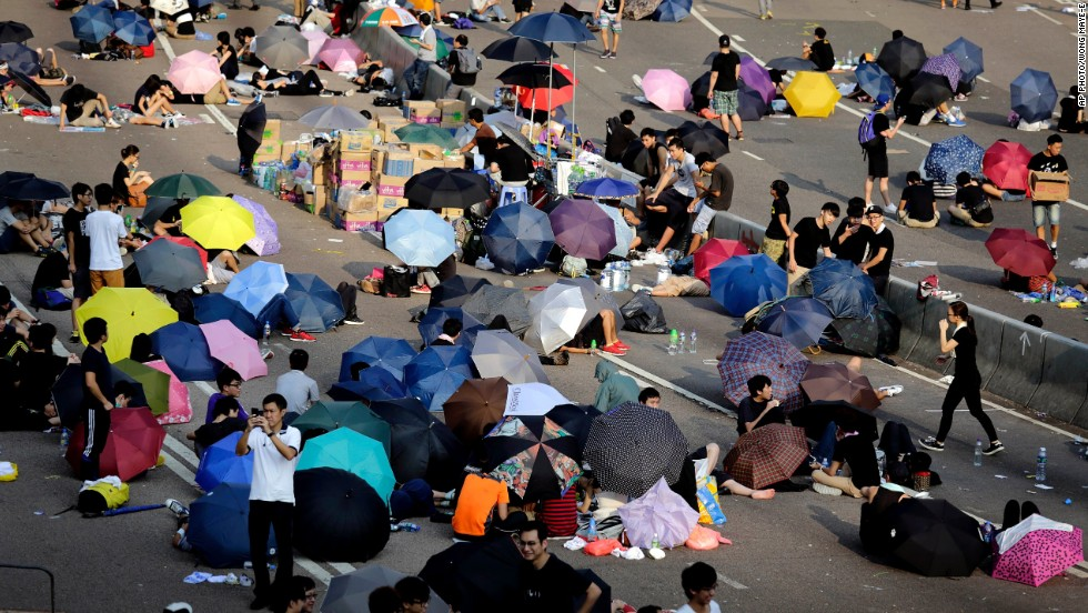 In daylight, umbrellas provide shade for pro-democracy activists. Students and activists rest on the street as they camp out in the main road in Hong Kong.