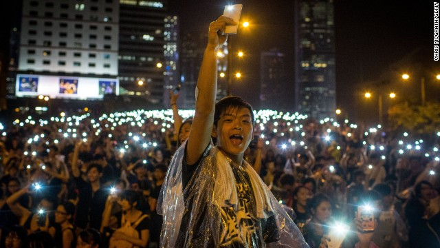 Protesters sing songs and wave their phones in the air after a massive thunderstorm passed over the Hong Kong Government Complex on September 30.