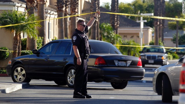 A police officer stands by the scene of a shooting in Bell Gardens, Calif., Tuesday, Sept. 30, 2014. Authorities say Mayor Daniel Crespo, of the Los Angeles suburb of Bell Gardens, has been shot to death and his wife is in custody. (AP Photo/Nick Ut)