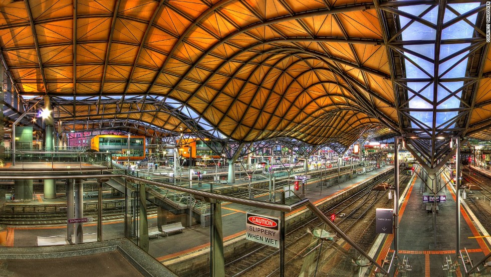 """Originally built in 1859, Melbourne's Southern Cross Railway station was renovated in 2005 to include an undulating roof that covers an entire city block. At the western end of the station is a colorful """"History of Transport"""" mural."""