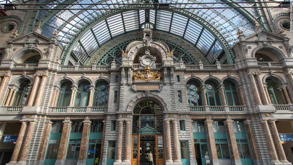 """The stone-clad Antwerpen-Centraal is such an eclectic mix of designs that it has no designated architectural style. Its vast dome covering the waiting room and vast iron and glass train shed earned the station the nickname """"Railway Cathedral."""""""