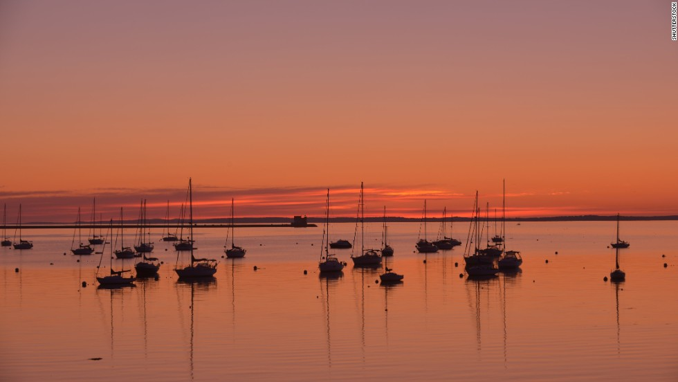 Yachts and sailboats sit anchored at sunrise in Maine's Rockland Harbor with the Rockland Breakwater Lighthouse in the background. The harbor offers ferries to Vinalhaven and other islands.