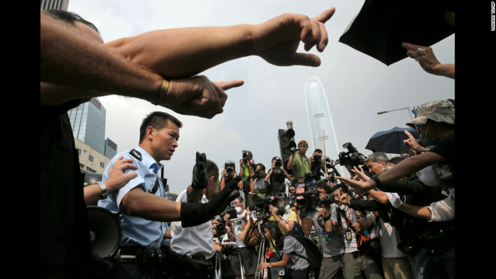 Police raise hands against protesters as an ambulance tries to leave the compound of the chief executive office in Hong Kong on October 3.