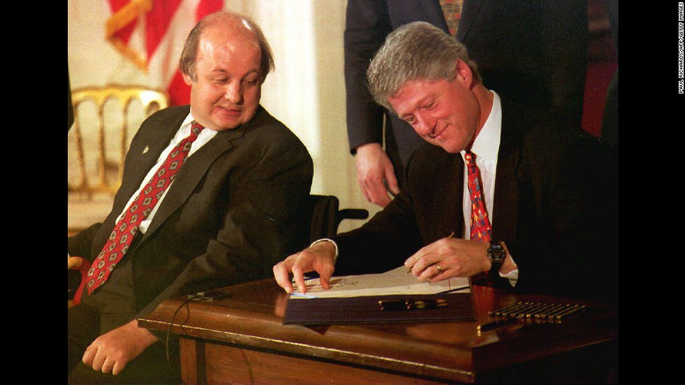 James Brady, the Reagan administration press secretary who was wounded during the 1981 assassination attempt, watches President Clinton sign the Brady Bill at the White House on November 30, 1993. The bill required a five-day waiting period for handgun purchases, ending a seven-year gun-control battle.