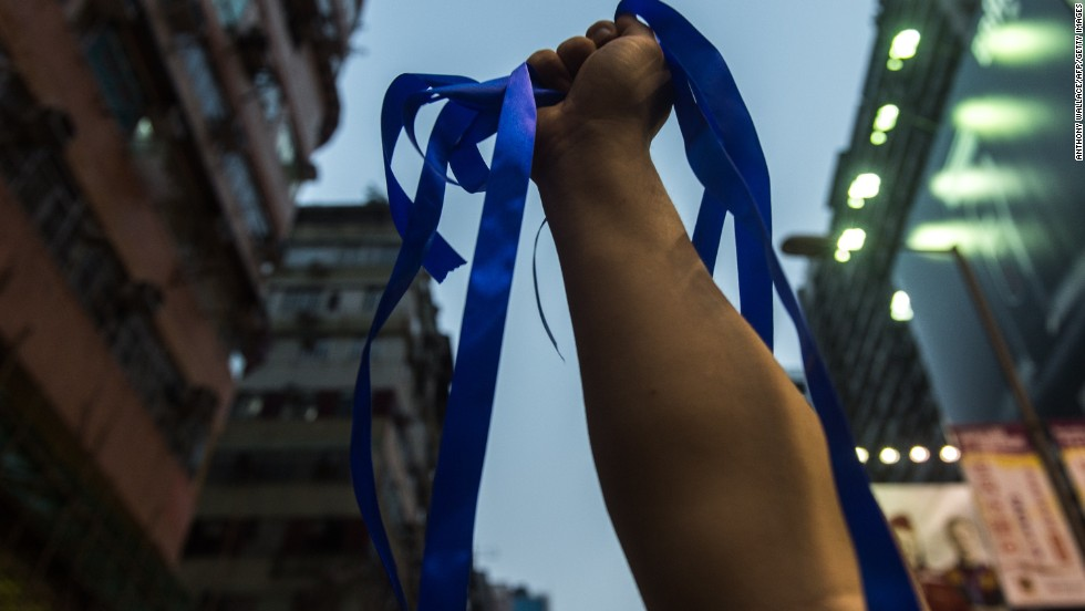 A pro-Beijing activist holds up blue ribbons for anti-Occupy Central protestors to collect as pro-government speeches are made in the Kowloon district of Hong Kong on October 4.