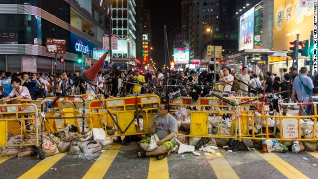 A man sits in front of a barricade built by pro-democracy protestors on October 4 in the Kowloon district of Hong Kong.
