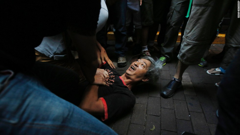 Pro-democracy student protesters pin a man to the ground after an assault during a scuffle with local residents in Mong Kok on October 4.