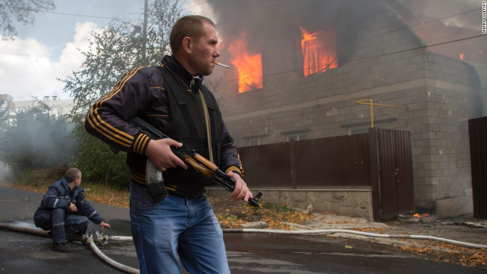 A pro-Russian rebel walks past a burning house after shelling in the town of Donetsk, Ukraine, on Sunday, October 5.