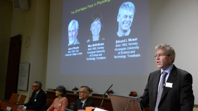 Professor Ole Kiehn, right, annouces at the Karolinska Institute in Stockholm the winners of the 2014 Nobel Prize in medicine for discoveries of cells that constitute a positioning system in the brain. Images of the winners U.S.-British scientist John O'Keefe and Norwegian husband and wife Edvard Moser and May-Britt Moser are projected on a screen at rear.