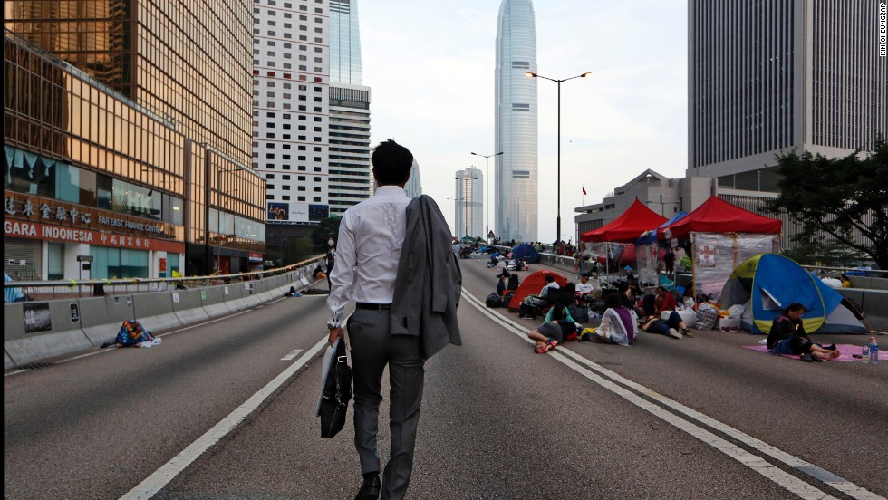 A man walks to work as pro-democracy demonstrators sleep on the road in the occupied areas surrounding the government complex in Hong Kong on October 6.