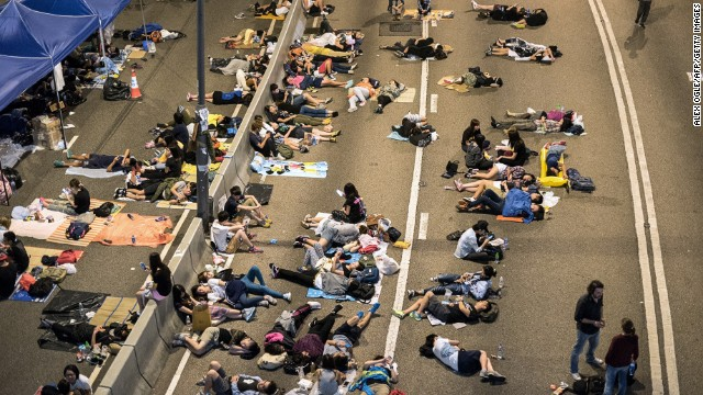 Pro-democracy protesters rest on a highway next to the central government offices in Hong Kong on October 6, 2014. Hong Kong's pro-democracy protesters remained stubbornly encamped on the streets early Monday, just hours before a government deadline to clear key thoroughfares they have blockaded for more than a week. The city's embattled leader Leung Chun-ying has warned he will 'take all necessary actions to restore social order' after a mass campaign for free elections that has seen tens of thousands of people pour onto the streets. AFP PHOTO / ALEX OGLE (Photo credit should read Alex Ogle/AFP/Getty Images)