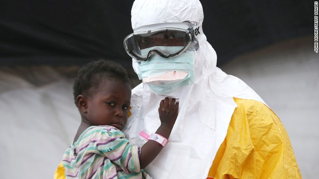 An MSF health worker in protective clothing holds a child suspected of having Ebola in the Paynesville, Liberia, treatment center on October 5.