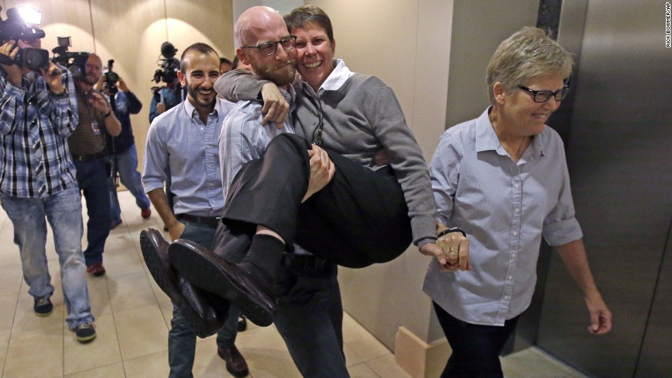 From left, plaintiffs Moudi Sbeity; his partner, Derek Kitchen; Kody Partridge; and Partridge's wife, Laurie Wood, celebrate after a news conference in Salt Lake City on October 6, 2014. The U.S. Supreme Court cleared the way for same-sex marriage in Utah when it declined to hear the state's appeal of a lower court ruling.