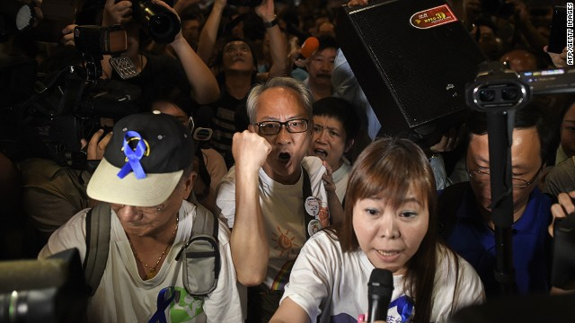 Letitia Lee See-yin (bottom-R), leader of the anti-occupy 'Blue Ribbon' group, is surrounded by pro-democracy protesters as she makes a speech in the Admiralty district of Hong Kong on October 7, 2014. Talks between the government and student leaders are progressing at a snail's pace, although even protest leaders are now acutely worried that further disruption could alienate supporters. AFP PHOTO / Ed JONESED JONES/AFP/Getty Images