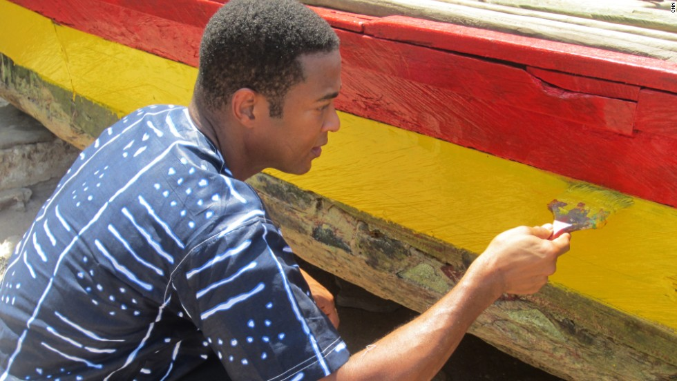 While visiting Elmina Beach, Lemon noticed an elderly fisherman painting his boat. He jumped in to help.