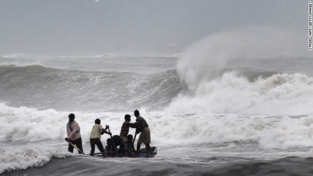 Indian fishermen negotiate their skiff through rough waves ahead of Cyclone Hudhud making expected landfall in Visakhapatnam on October 11, 2014. India on October 11 began evacuating thousands of people from fishing villages as it braced for Cyclone Hudhud barrelling towards its east coast, officials said. AFP PHOTO/STR (Photo credit should read STRDEL/AFP/Getty Images)