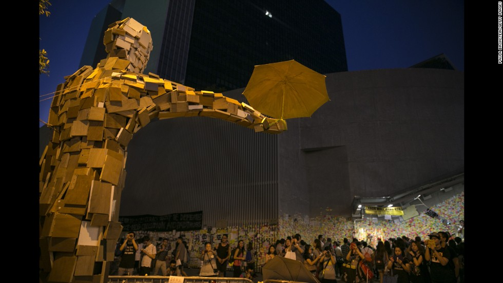 "People gather beneath the statue ""Umbrella Man,"" by the Hong Kong artist known as Milk, which has become a symbol at the protest site, on Saturday, October 11, in Hong Kong."