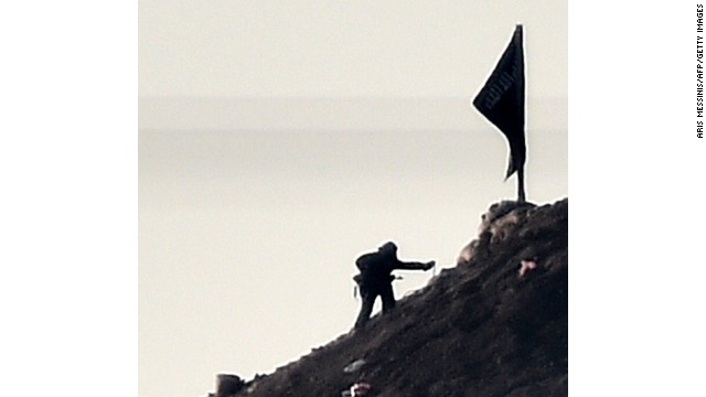 Caption:Alleged Islamic State (IS) militants stand next to a black IS flag atop a hill in at the eastern part of the Syrian town of Ain al-Arab, known as Kobane by the Kurds, as seen from the Turkish-Syrian border in the southeastern town of Suruc, Sanliurfa province, on October 7, 2014. Fresh air strikes by the US-led coalition hit positions held by Islamic State jihadists in the southwest of the key Syrian border town of Ain al-Arab (Kobane), according to an AFP journalist just across the border in Turkey. The strikes came a day after the extremists pushed into Kobane, seizing three districts in the city's east after fierce street battles with its Kurdish defenders. AFP PHOTO / ARIS MESSINIS (Photo credit should read ARIS MESSINIS/AFP/Getty Images)