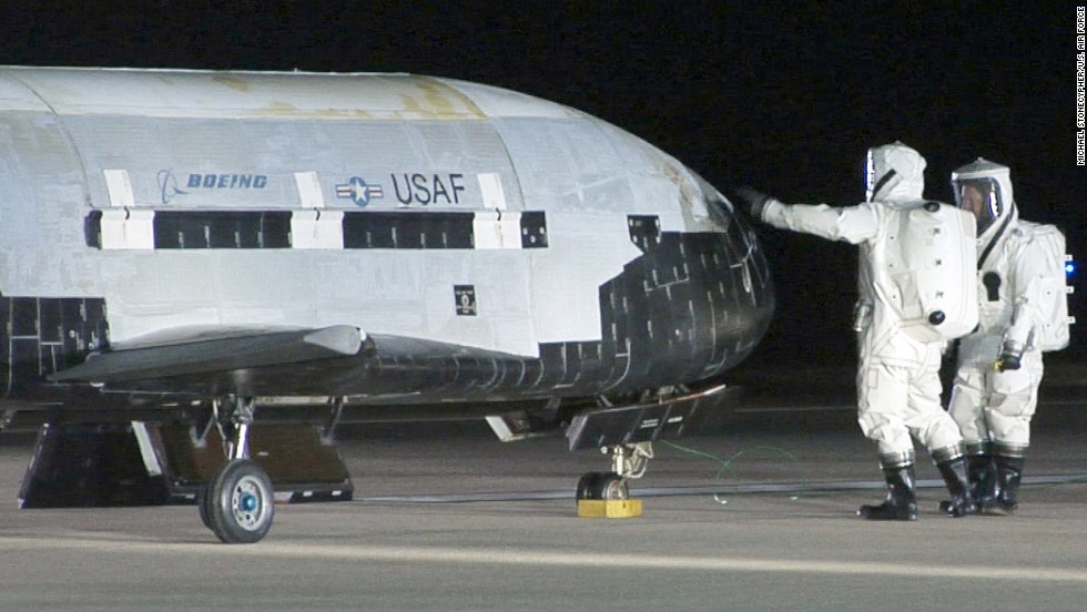 Technicians in self-contained atmospheric protective ensemble suits conduct initial checks on the X-37B after its landing on December 3, 2010.