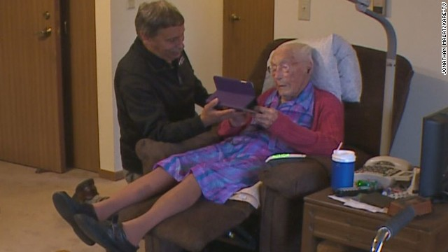 Anna Stoehr, a new Facebook user at age 114, looks at an iPad with the help of friend, and Verizon salesman, Joseph Ramireza.