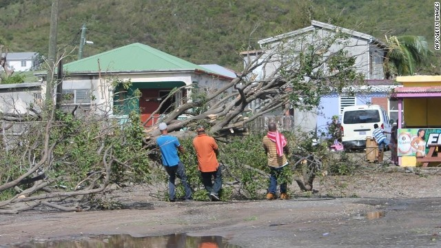 People clear trees from the road on the island of St. Martin in the aftermath of Hurricane Gonzalo