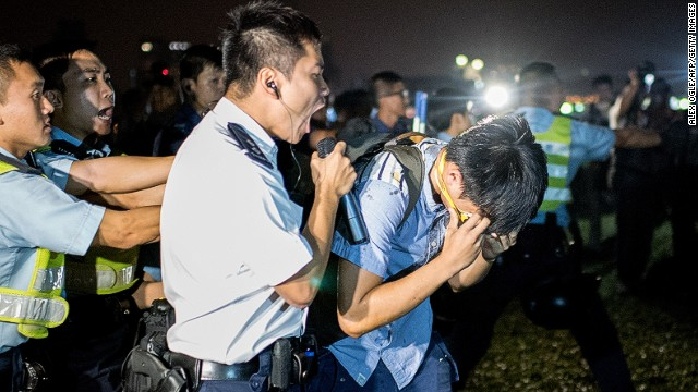 A police officer shouts into a microphone after a protester was hit with pepper spray on October 15.