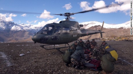 An injured survivor of a snowstorm is assisted by Nepal army personnel near the Annapurna range of the Himalayas.