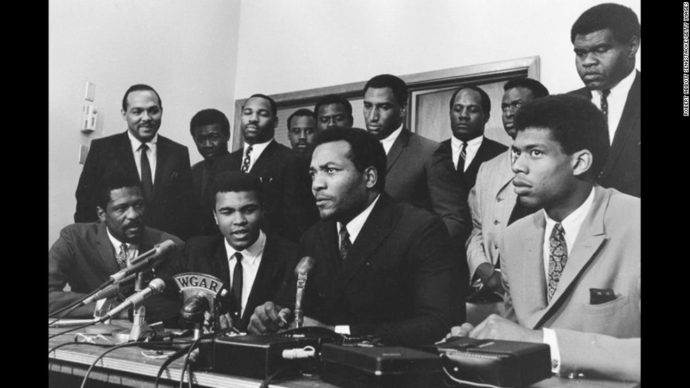 As a conscientious objector to the Vietnam War, Ali refused induction into the U.S. Army in April 1967. Here, top athletes from various sports gather to support Ali as he gives his reasons for rejecting the draft. Seated in the front row, from left to right, are Bill Russell, Ali, Jim Brown and Kareem Abdul-Jabbar.