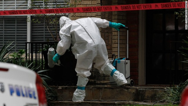 A man dressed in protective hazmat clothing treats the front porch of an apartment where a second person diagnosed with the Ebola virus resides in Dallas, Texas, on Sunday, October 12. A female nurse working at Texas Heath Presbyterian Hospital, the same facility that treated Thomas Eric Duncan, has tested positive for the virus.
