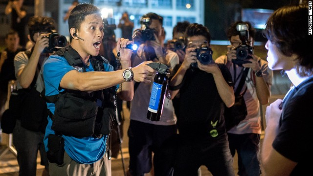TOPSHOTS  A police officer threatens to pepper spray a pro-democracy protester as demonstrators tried to occupy a main road in Hong Kong on October 15, 2014. Hong Kong has been plunged into the worst political crisis since its 1997 handover as pro-democracy activists take over the streets following China's refusal to grant citizens full universal suffrage. AFP PHOTO / ALEX OGLEAlex Ogle/AFP/Getty Images