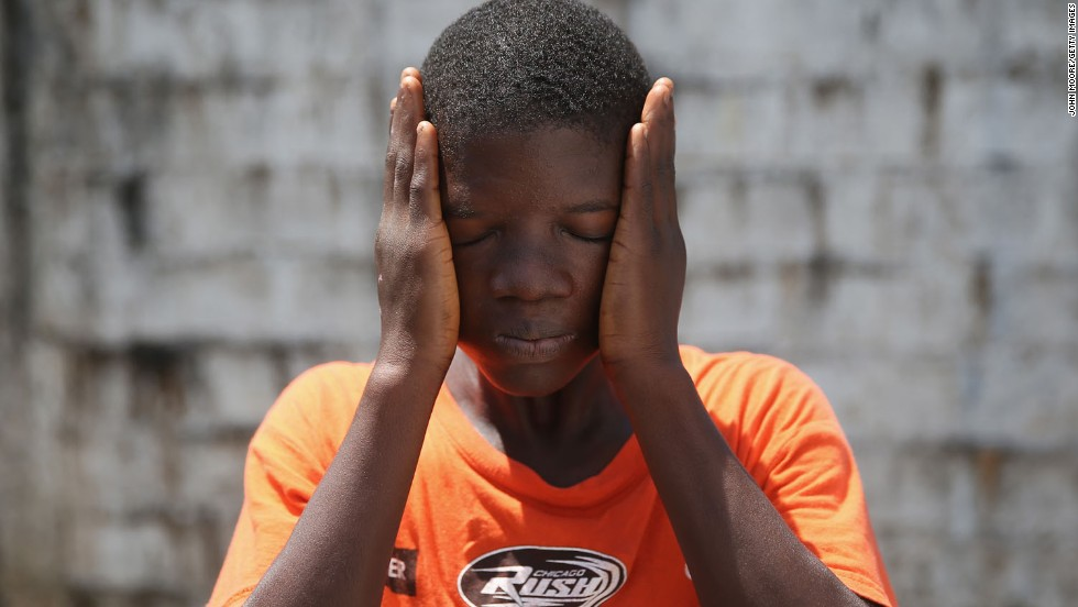 Ebola survivor Jeremra Cooper, 16, wipes his face from the heat while in the low-risk section of the Doctors Without Borders (MSF) Ebola treatment center in Paynesville, Liberia, on Thursday, October 16. The eighth grade student said he lost six family members to the Ebola epidemic before coming down sick with the disease himself and being sent to the MSF center, where he recovered after one month.
