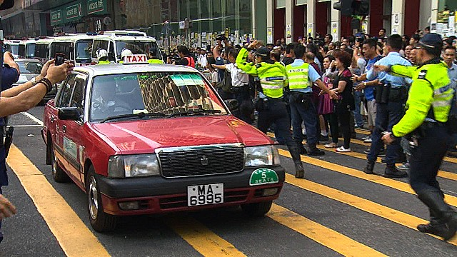 Hong Kong police allow cars to roll down Nathan Street in the Mong Kok business district, October 17, 2014.