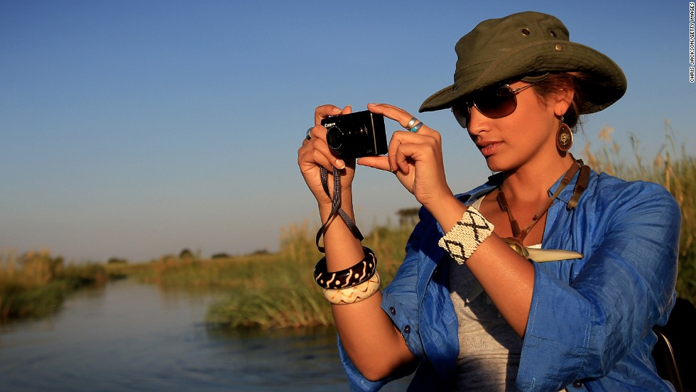 A woman on a boat ride in the Okavango Delta viewing various wildlife. Botswana relies heavily on tourism, and ecotourism in Botswana is said to contribule 4-5% towards the country's GDP.