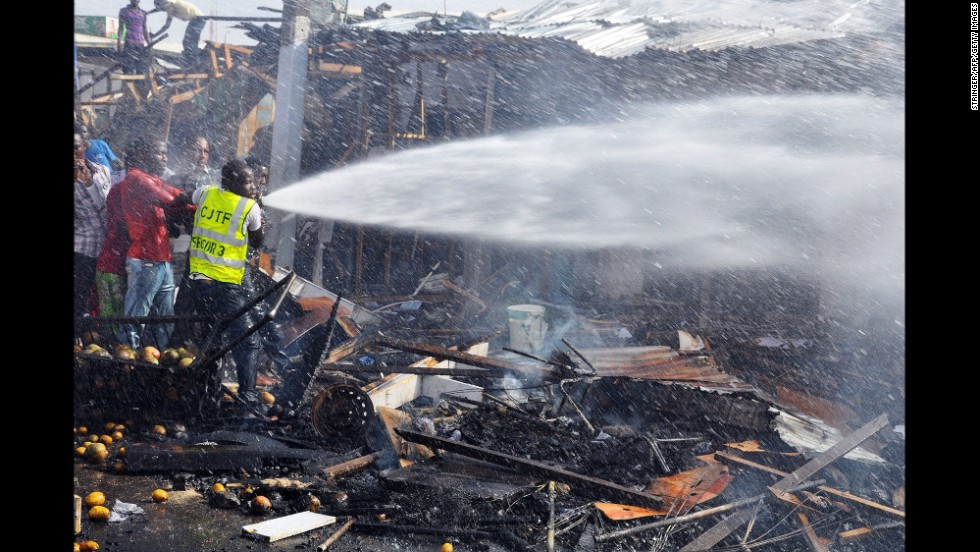 Rescue workers try to put out a fire after a bomb exploded at the busiest roundabout near the crowded Monday Market in Maiduguri on July 1, 2014.