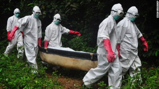 A burial team in protective gear carry the body of woman suspected to have died from Ebola virus in Monrovia, Liberia. Saturday, Oct, 18, 2014. The death toll from Ebola will rise this week to more than 4,500 people from the 9,000 infected and the outbreak is still out of control in three West African nations, a top official with the U.N. health agency said   (AP Photo/Abbas Dulleh)