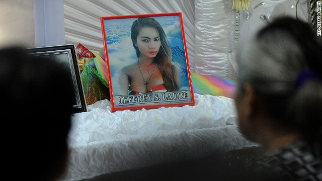 Friends and relatives of Filipino transgender resident Jeffrey Laude look on alongside his coffin and photograph in the northern Philippine city of Olongapo on October 14, 2014. Police said Laude was suspected to have been killed by a US Marine inside an Olongapo hotel on October 12, 2014. The suspect has been detained by the US authorities aboard the USS Peleliu, which is docked at the Olongapo port after US Marines took part in joint military exercises in the Philippines September 29-October 10, 2014. AFP PHOTO / Jay DIRECTOJAY DIRECTO/AFP/Getty Images