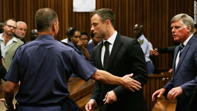 Oscar Pistorius, center, is led out of court in Pretoria, South Africa, Tuesday, Oct. 21, 2014.  Pistorius received a five-year prison sentence for culpable homicide by judge Thokozile Masipais for the killing of his girlfriend Reeva Steenkamp last year (AP Photo/Themba Hadebe)