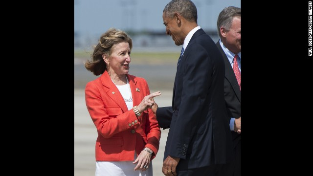 US President Barack Obama greets North Carolina Democratic Senator Kay Hagan upon arrival at Charlotte Douglas International Airport in Charlotte, North Carolina, August 26, 2014.