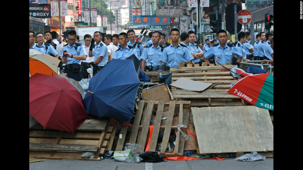 Riot police stand guard near a barricade in a protester-occupied area on Wednesday, October 22.