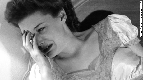 circa 1955: A woman crying as she looks at her bedside clock. (Photo by Three Lions/Getty Images